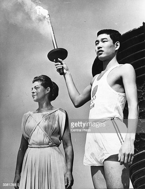 Yoshinori Sakai, born at Hiroshima on the day the first atomic bomb was dropped on the city, holding the Olympic torch beside Greek actress Aleka...