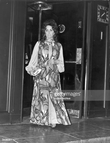 British actor Elizabeth Taylor, wearing a beaded maxidress, exits a revolving door.