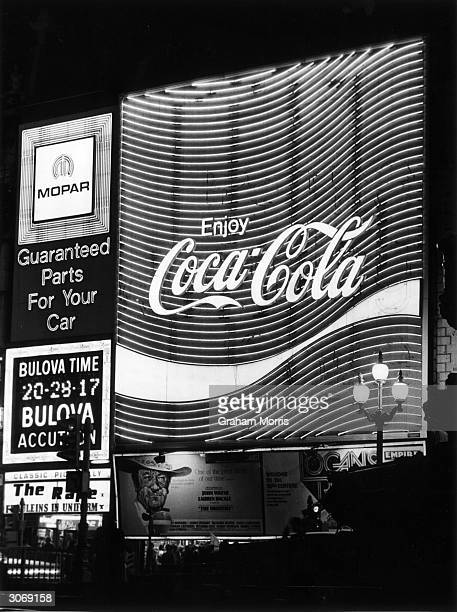 The Coca Cola neon sign in London's Piccadilly Also advertised are Bulova watches and Mopar car parts