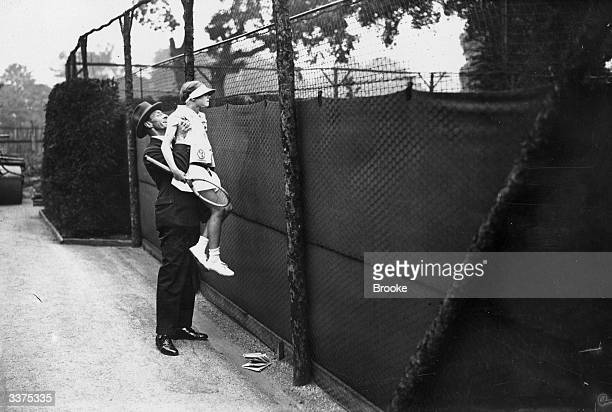 11yearold Diana Waring is lifted up for a view of the Junior Tennis Championships of Great Britain at the All England Lawn Tennis Club London