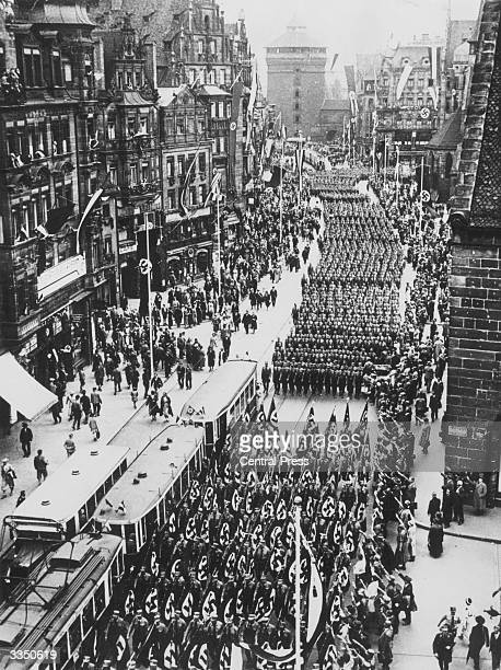 Members of the Nazi party marching through the streets of Nuremberg carrying flags bearing a swastika