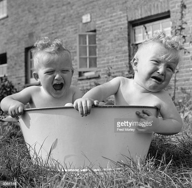 Young twins Martin and Peter Thompson who took first prize at a local baby show for the second year in succession sharing a bath in the garden of...