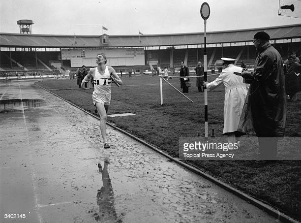 British athlete Roger Bannister crossing the finish line at the end of the 400 metres relay during the International Athletics Meeting between...