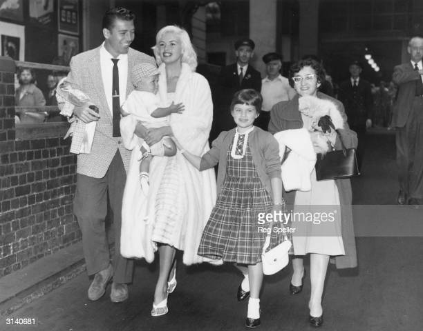 Hollywood sex symbol Jayne Mansfield arrives at Euston Station in London, en route to Blackpool to turn on the city's famous lights. With her are her...