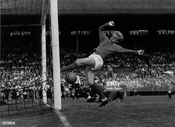 Scotland and Manchester United footballer Denis Law scoring during a game against Fulham Law was signed for Huddersfield by Bill Shankly and played...