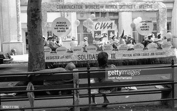 New York Two people relax on a park bench as a float filled with protesting laborers from the Communications Workers Of America Union heads down...