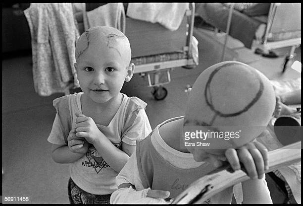 5yearold Anya Petrushkova who was diagnosed with lymphosarcoma stands behind 4yearold Andrey Sabirov from Gomel who rests his head on the side of his...