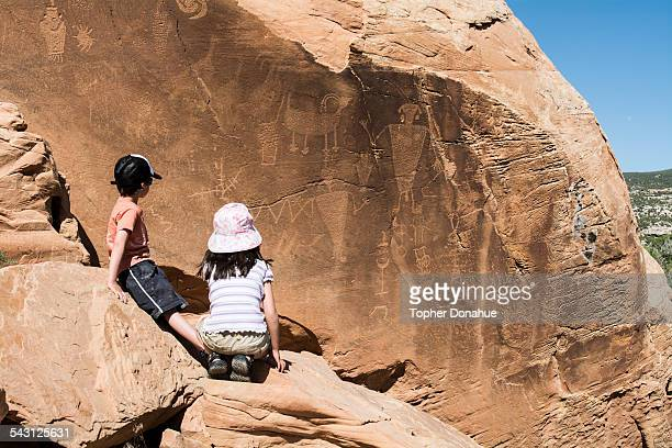 5-year-old boy-girl twins study a wall of pictographs.
