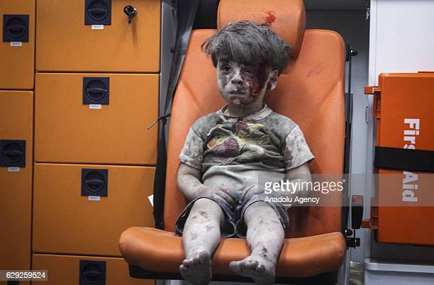 5yearold wounded Syrian kid Omran Daqneesh sits alone in the back of the ambulance after he got injured during Russian or Assad regime forces air...