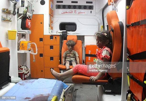 5yearold wounded Syrian kid Omran Daqneesh sits with his sister in the back of the ambulance after they got injured during Russian or Assad regime...