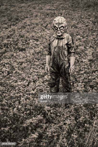 60s style alien standing the the field - scaredastronaut stock pictures, royalty-free photos & images