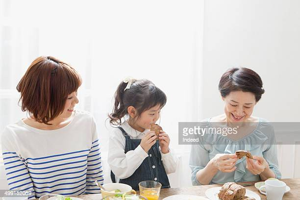60th generation grand mother and 20th generation mother and 5-9 year old daughter who sit at a table