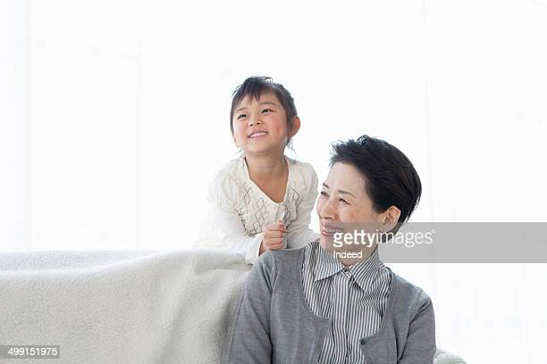 60th generation grand mother sitting on a sofa with her 5-9 year old grand daughter