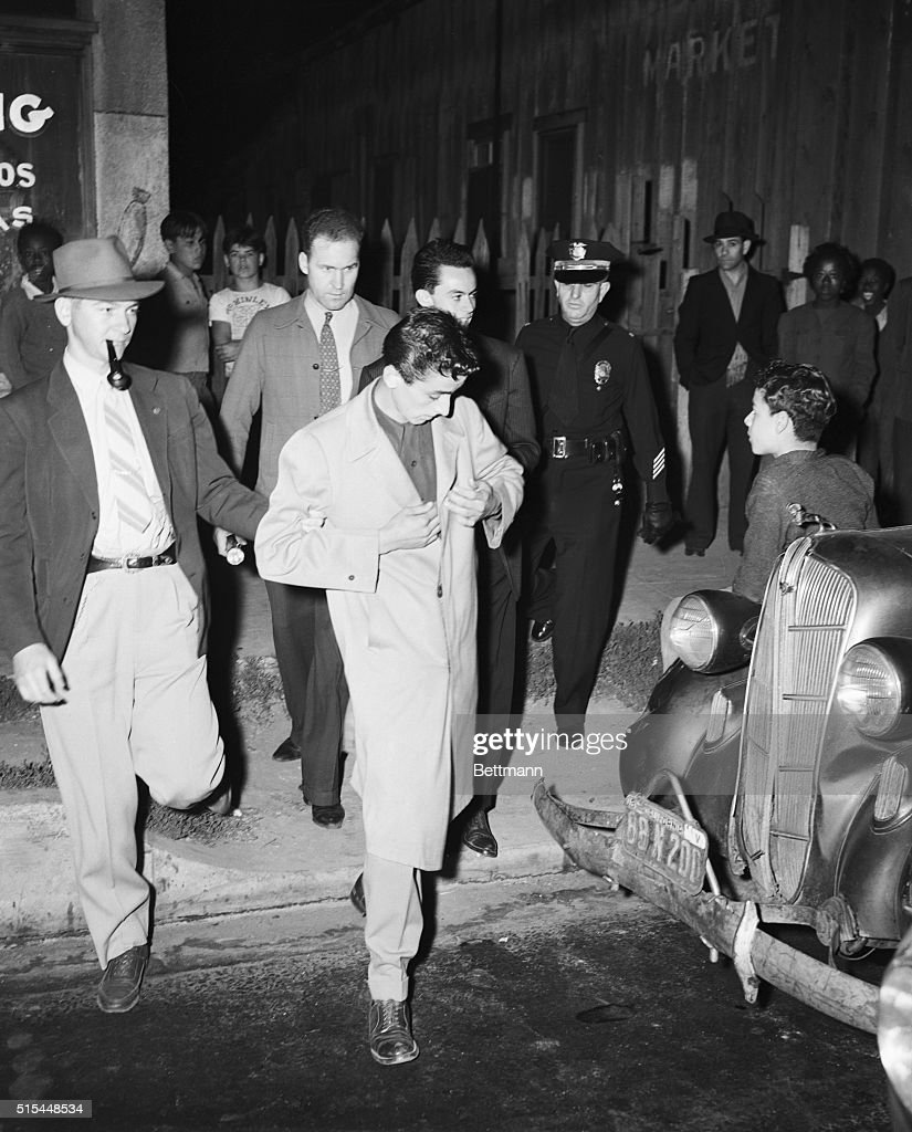 Watts, California- Police officers take this zoot suit clad youngster into custody after the sixth day of undeclared war on the reat pleat in Los Angeles. More than 112 persons have been injured, some of them seriously, in the frequent clashes between wearers of the glad plaid and servicemen.