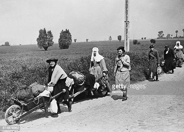 These refugees ever fearful that at any moment a German plane might swoop down on them to do a strafing job hurry along a road as they flee deeper...
