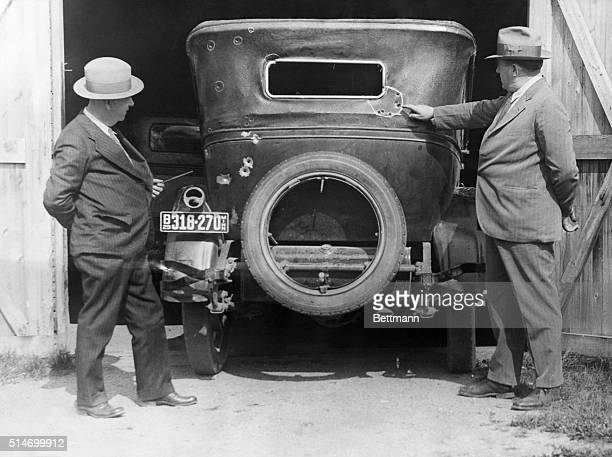 International Falls, MN: Sheriff Hugh Reidy of Koochiching County, MN, at right, pointing to the holes made by the sawed off shot gun in hands of...