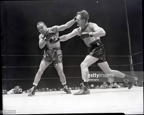 New York, NY: After Lee Savold delivered a hard right, former heavyweight champion Joe Louis is shown returning a left during their scheduled fifteen...