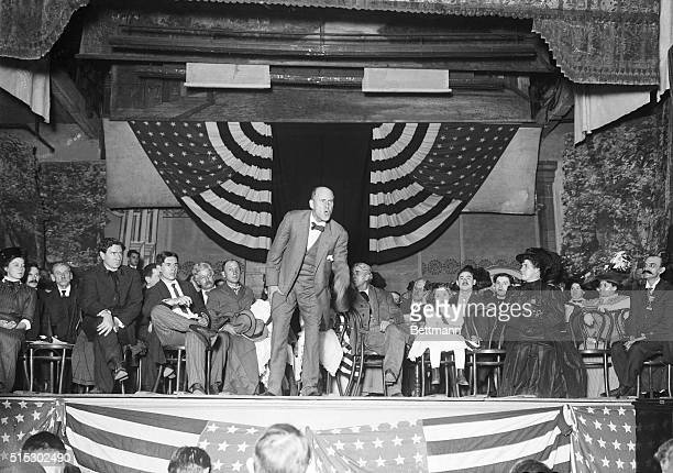 Canton, Ohio: Eugene Debs delivers an anti-war speech. He is shown on a small platform, surrounded by seated men, women and children. A flag-banner...