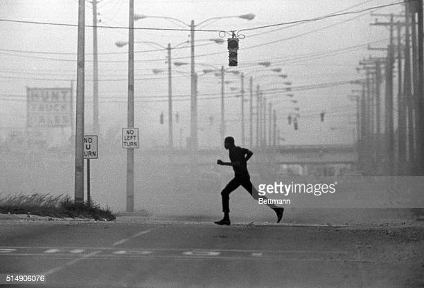 Miami, FL- A silhouetted Negro youth runs across the street in an area teargassed by law enforcement officials. Police exchanged gunfire with...