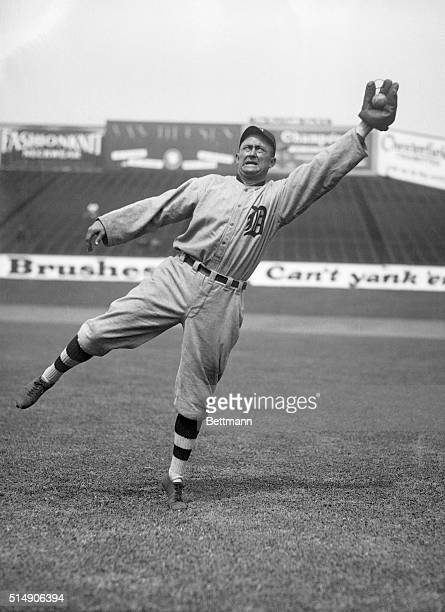 Photo shows Ty Cobb fielding, leaping in the air for a ball.