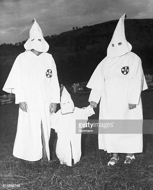 A father mother and their child all correctly attired in Ku Klux Klan regalia pose on the sidelines during KKK meeting on Stone Mountain near Atlanta...
