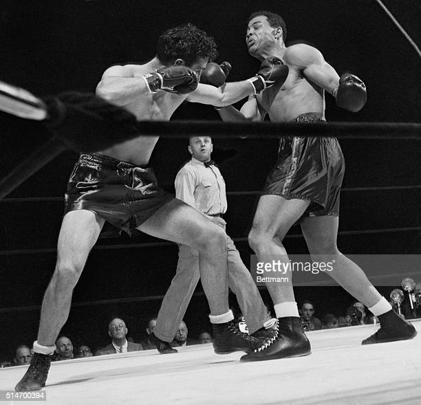 New York: Challenger Billy Conn, at left, stings champion Joe Louis with a left jab to the throat early in their scheduled fifteen round battle for...