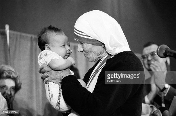 Mother Teresa holds up an unidentified baby for a close look while attending the National Right to Life convention 6/21 Mother Teresa winner of the...