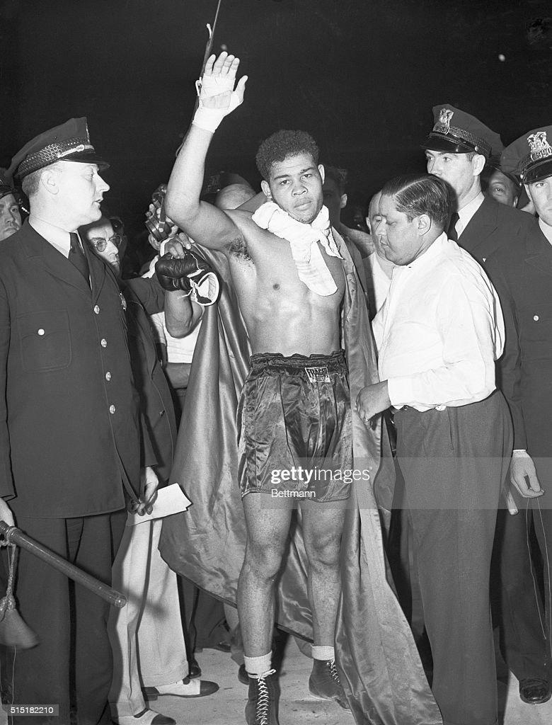 Chicago, IL- Joe Louis, with hand upraised, is pronounced the new heavyweight champion of the world, after his eighth round knockout of Jimmy Braddock in Chicago.