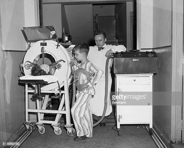 6/22/1949New York NY Dr Harry Seanor of Willard Parker hospital looks on as polio victim Mark Fresco wearing new 'Monaghan' one pound iron lung talks...