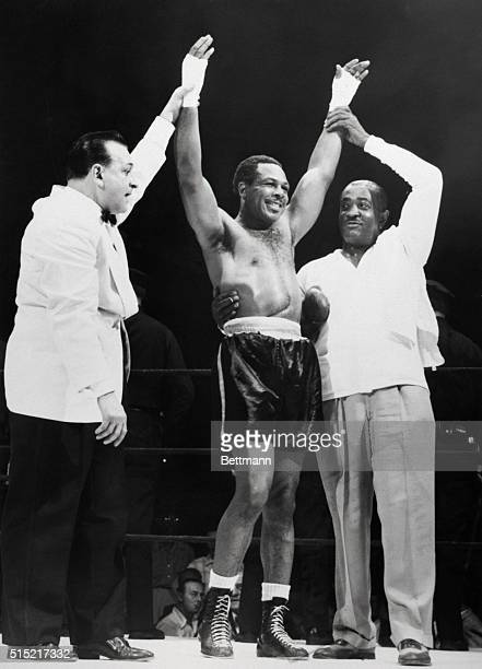 6/22/1955New York New York 'Winner and still champion' Archie Moore as his hands are raised in the traditional sign of victory by ring announcer...