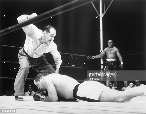 6/22/1955New York NY Middleweight champ Carl 'Bobo' Olson sprawls full length on the canvas as referee Ruby Goldstein counts him out at 119 of the...