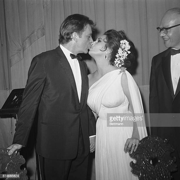 Actor Richard Burton kisses his beautiful actresswife Elizabeth Taylor following their successful benefit performance of prose and poetry readings at...