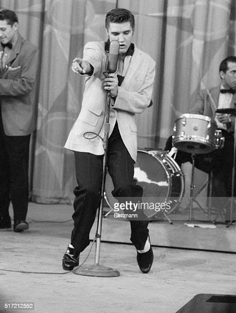 A pointing finger gives Elvis Presley a dramatic contact with his audience as he clutches the microphone with his other hand Fancy footwork is part...
