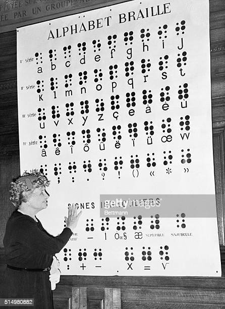 6/23/1952Paris France Hellen Keller points to a chart of the braille alphabet during her speech at the Sorbonne commemorating the 100th anniversary...