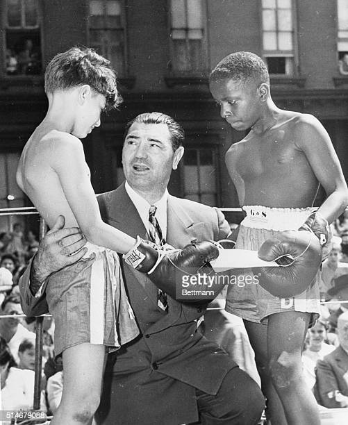 Anthony Lotito and Oscar Goodjoines both 11 get congratulations from Jack Dempsey for their sportsmanship after fighting to a draw for the...