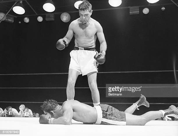 New York, NY- Middleweight champion Ray Robinson flattens on the canvas after swinging, missing, and falling, in the thirteenth session of his...