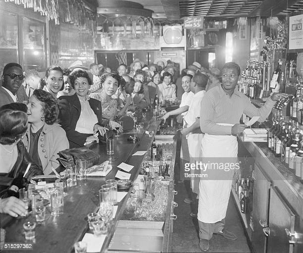 6/25/1953New York NY Sugar Ray Robinson tends a crowded bar on Seventh Avenue between 122nd and 123rd Streets