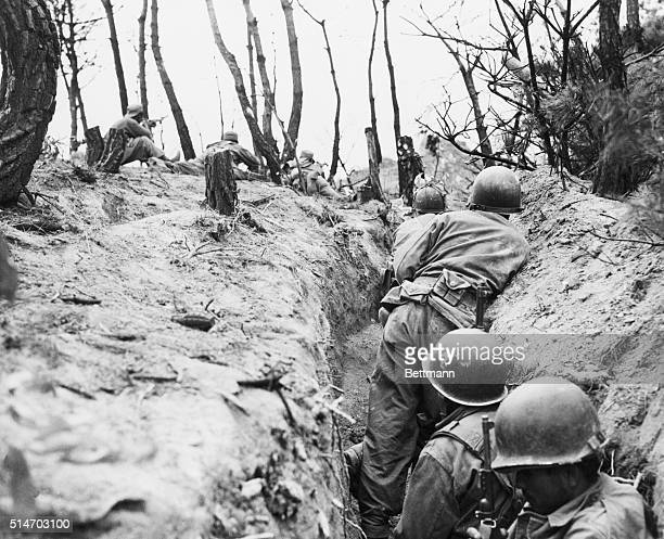 Puerto Rican infantrymen take cover in an abandonded enemy trench durign action on the battle front As world capitals buzzed with peace rumors...