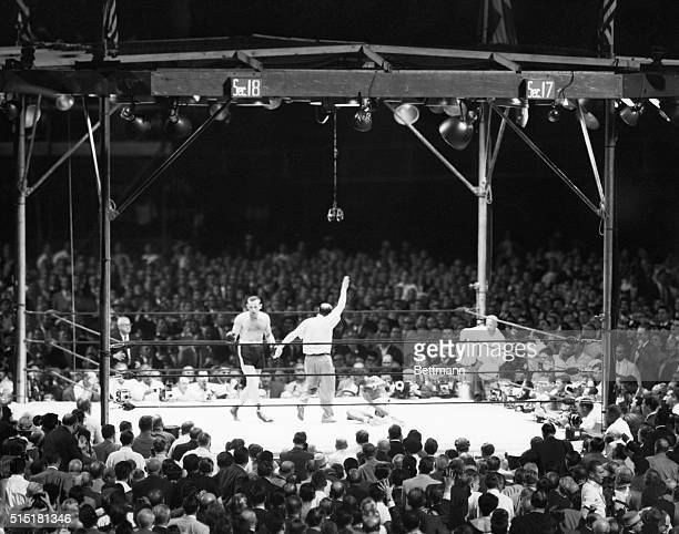 6/26/1959New YorkNYAs the ringside gallery rises to its feet to cheer referee Ruby Goldsteinstanding over a battered Floyd Patterson sprawled on the...