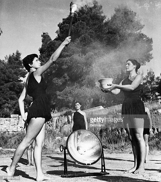 6/28/1952Olympia Greece Young Greek girls dressed in appropriate Ancient Greek costumes light the Olympic torch The flame is created through the sun...
