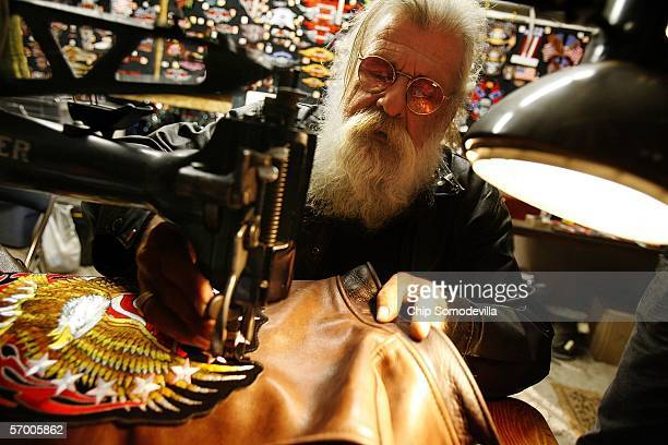 62yearold Lord PM Christ uses a 1939 Singer sewing machine to put a patch on a leather motocycle jacket at Soponick's Cabbage Patch Bar during the...