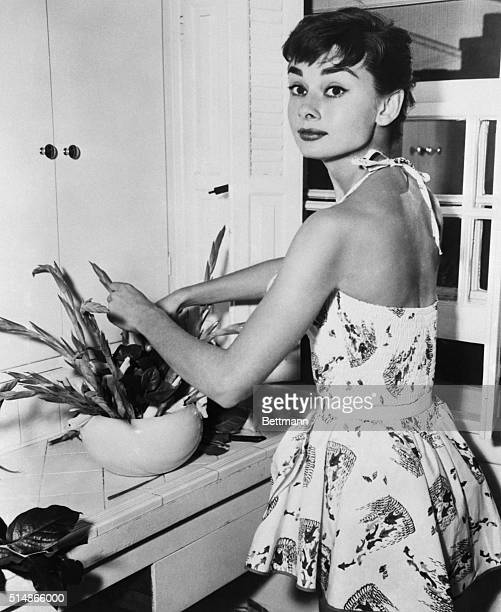 6/30/1954New York NY Pixyish Audrey Hepburn Academy Award actress beats the Manhattan heat with a cool play suit as she does chores in her New York...