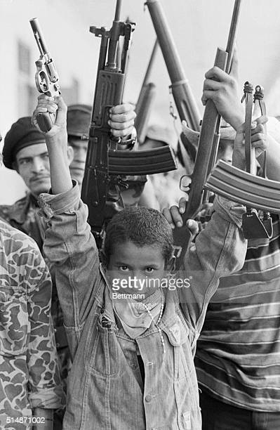 Masaya, Nicaragua: A young Sandinista guerrilla holds a slingshot in one hand and a pistal in the otheras he is surrounded by his older comrades in...