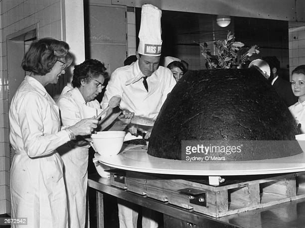 A 650lb Christmas pudding being cut by Mrs Dorothy Hayward kitchen superintendent at Great Ormond Street Hospital for Children and Mr John Neville...