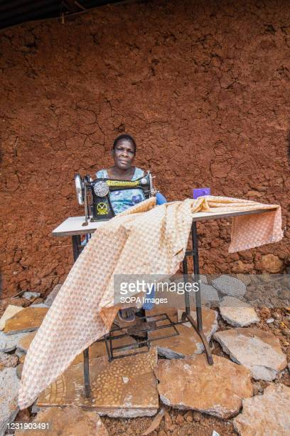 Year-old Florence Osupa, a local tailor and a resident of Kibera slums waits for her customers outside her demolished business stall by the Kenya...
