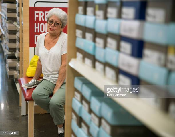 65-years-old active senior woman shopping footwear in the clothing retail store