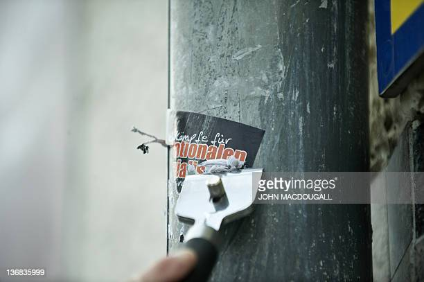 COLE 66yearold antiNazi activist Irmela MensahSchramm scrapes a Nazi sticker off a drainpipe in eastern Berlin's Lichtenberg district December 20...