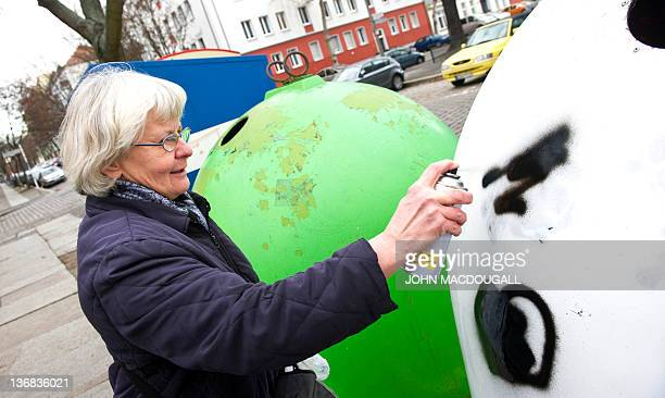 COLE 66yearold antiNazi activist Irmela MensahSchramm sprays paint over a nazi symbol on a recycling bin in eastern Berlin's Lichtenberg district...