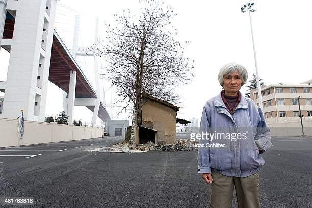68yearold Shi Yuji poses in front of her house which will be destroyed to make way to a Shanghai World Expo 2010 parking lot under Nanpu bridge on...