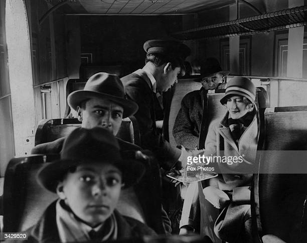 A cabin steward serves drinks to the passengers on an early French airliner providing a service to and from Le Bourget